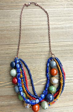 Necklace is chunky and not heavy! Made with blue stone, glass, seed beads and ceramic beads layered with copper metal. Copper chain and spacer beads. Necklace colors are a muted earthy tone in red, gr