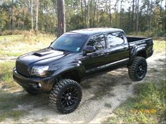 Double cab and lifted Toyota Tacoma murdered out with black wheels, tinted windows, and a perfect sized lift.