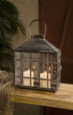 Drake Wide Candle Lantern - This antiqued wrought iron candle lantern features a woven metal design over glass, its versatile look works with a variety of interior styles. The Drake lantern holds two pillar candles or create your own unique terrarium look.