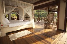 A stunning villa in the caribbean by Nomade Architettura http://www.nomadearchitettura.com/#all  canopy bed overlooking the sea, timber floor and timebr roof