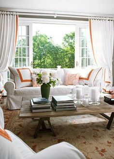 Sweet orange accents in a light living room are fun and inviting. - Traditional Home ®/ Photo: John Bessler / Design: Sophie Thibon Interiors