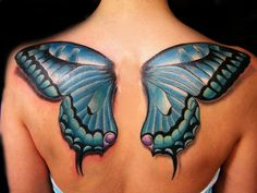 A tattoo of blue butterfly wings across the upper back and shoulders. The tattoo artist has given the wings a shadow to create the illusion that the wings are above the skin.