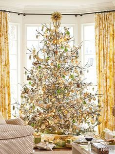 """When you love a specific color scheme, your decorating philosophy should be """"the more the merrier."""" Pretty twinkling lights, shiny gold and green ornaments, and kid-friendly DIY garland are finished off with a sprinkling of artificial snow. A unique and eye-catching tree topper is the perfect final touch. Editor's Lighting Tip: Thin out branches before decorating to make each light and ornament have more presence."""