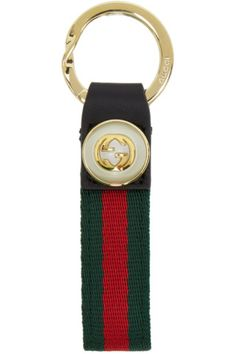 Nylon webbing keychain striped in green and red. Black leather trim featuring faux-pearl and logo plaque at end. Logo-engraved keyring fastening. Gold-tone hardware. Tonal stitching. Approx. 4 length x 1 width.