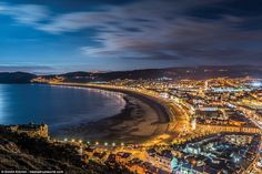 Bucket and spades at the ready: The bright lights ofLlandudno glow as the sun sets. It is a popular seaside destination with thousands of tourists flocking to the beaches each year