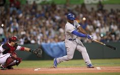 The Dodgers' Yasiel Puig fouls a ball as the Diamondbacks' catcher Miguel Montero reaches out in the first inning of Major League Baseball opening game between the Los Angeles Dodgers and Arizona Diamondbacks at the Sydney Cricket ground in Sydney, Saturday, March 22, 2014. (AP Photo/Rick Rycroft)