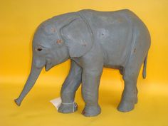 "A very interesting form is this turn of the century standing Elephant, he measures 14 1/2"" Ht., 5 1/2"" W, and 19"" overall from the tip of his trunk to his tail. There is some minor paint flecking which could be easily touched up if you so desire."