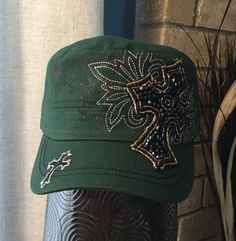 This dark green cadet cap features a black screen printed pattern across the front of the hat, along with silver embroidery that follows the pattern. There is a small cross embroidered in black and silver on the front left of the bill and a black fabric cross embellished with iridescent and metallic beading that covers part of the front and bill of the cap.  - Three-panel construction. - Embroidered design. - Screen printed design. - Iridescent and metallic beads.