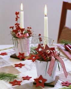 Arrangements of ilex berries, pine, red stars and candles