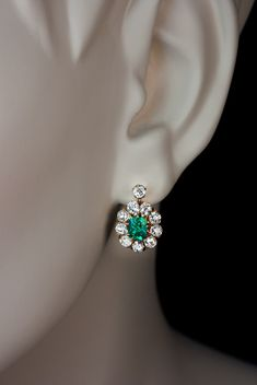 Vintage Colombian Emerald and Diamond French Clip Earrings circa 1910. The gold earrings are centered with cushion cut sparkling Colombian emeralds of an e