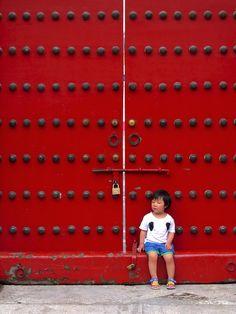 Petit garçon assis sur le bas d'une grande porte rouge  #Cite Interdite #Pekin