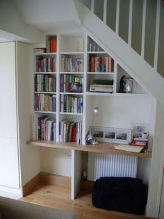 Simple and elegant space saving staircase design: inspiring workspace below white staircase with black cushion interior design space saving stairs ideas Shelves Under Stairs, Stair Bookshelf, Space Under Stairs, Bookshelf Ideas, Book Stairs, Home Office, Office Desk, Space Saving Staircase, Workspace Inspiration