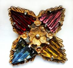 Button with foil backed, jewel colored glass stones which are prong set in gilt metal.