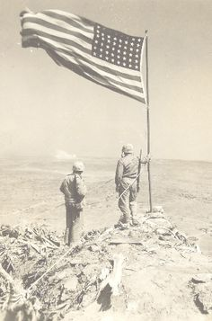 Two Marines assess the area while standing next to the raised flag on Mount Suribachi, 1945. LSTs - tank landing ships, lined up along the assault beaches to the right, the rest of Iwo Jima stretches out in the distance to the left.