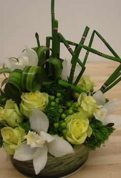 This is an arrangement featuring white orchids, green roses and horsetail.  See our entire selection at www.starflor.com.  To purchase any of our floral selections, as gifts or décor, please call us at 800.520.8999 or visit our e-commerce portal at www.Starbrightnyc.com. This composition of flowers is generally available for same day delivery in New York City (NYC). OR014