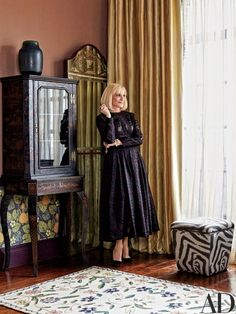 Stylesetter Lorry Newhouse (wearing a dress she created for her eponymous fashion line and jewelry by David Webb) stands in the Manhattan apartment she shares with her husband, Mark Newhouse, a publishing executive; the duplex was decorated in collaboration with Rain Phillips.
