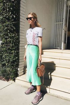 """Give a pretty satin skirt the street style treatment and wear it with """"ugly"""" sneakers and a T-shirt."""