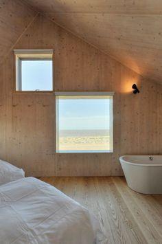 Plywood i väggar och tak tillsammans med snedtak och trägolv ger det här sovrummet en mysig känsla av koja.