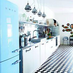 Paolo et Daniela ont imaginé pour leur appartement niçois une cuisine tout en longueur qui associe les styles professionnel et vintage. Dessinée par la designer Paola Navone. Le style industriel apparaît sous les traits d'une crédence et une longue barre en inox sur laquelle sont accrochés des ustensiles et une série de suspensions industrielles en fonte d'aluminium chinées. Le métal étant omniprésent. Réfrigérateur bleu azur Smeg au style vintage.