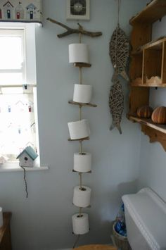 toilet roll holder made from drift wood and old rope. simply twist the wood round to remove old rolls and when it's all empty fill it up again!