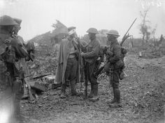 MINISTRY INFORMATION FIRST WORLD WAR OFFICIAL COLLECTION (Q 809) Men of the Leicester Regiment with wounded German prisoner. Note wire cutter attached to rifle; near Contalmaison, July 1916