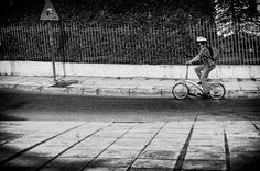 Cycling up the hill This is another one of my Athens shots, while sitting on the back of a bike. I took this one of this cyclist cycling up this not so steep hill, because he looked interesting on his tiny little bicycle. I like shooting moving objects and I found that doing so while on a moving vehicle was quite challenging, making the anticipation of a well timed shot even more intense for me. My Athens, Another One, Street Photographers, Greece, Vehicle, Cycling, Shots, Objects, Bicycle