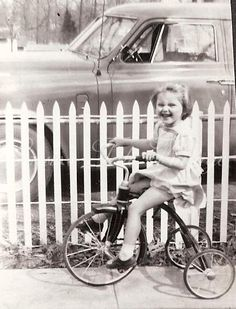 Tricycle, old car, white picket fence. Classic.
