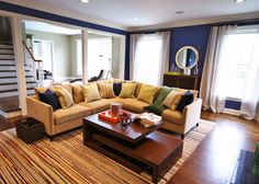 An L-shaped sofa frames in the conversation area in this transitional living room, where a colorful striped rug adds graphic energy. Dark blue walls are a rich and unique neutral backdrop for the space.