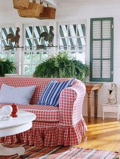 Farmhouse Accessories ~ A collection of baskets, a pair of weather vanes, a chicken coop door, and a rustic hand pump pack a punch of vintage style in the sunny family room. The comfy, skirted sofa provides a feminine flair.