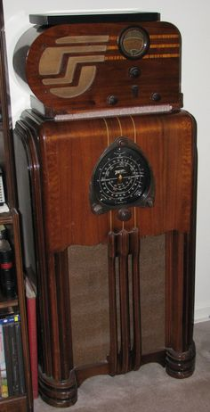 A beautiful big black dial Zenith console radio with an Art Deco Philco radio on top of it.: