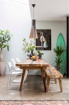 A casual dining space with modern light and turquoise surfboard