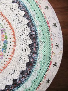 Great idea for a pillow or stool... take a large doily and decorate it with strips of lace, fabric, and an embroidered vintage doily for the middle.