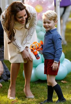 Prince George looks in awe as giant bubbles are blown into the air by one of the children's entertainers at the party Catherine, D...