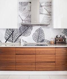 plan de travail cuisine en quartz blanc, crédence feuilles et armoires noyer