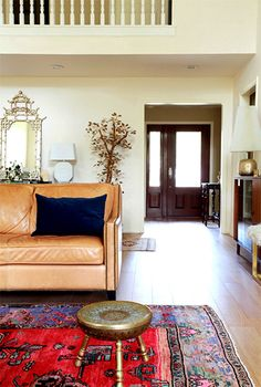 Design Crisis Erin Williamson living room, tan leather sofa, Persian rug, brass, chinois mirror
