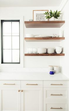 All white kitchen with wood accents, love these floating shelves and the pretty black windows