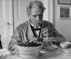 Dr. Albert Schweitzer, medical missionary & humanitarian, sitting at table eating bowl of cherries.