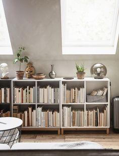 Lave hyller fulle av bøker og med pyntegjenstander og planter på toppen.