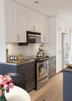 Darker color bottom cabinets, maybe top cabinets without doors and with the darker color on the inside? ALWAYS love the white/gray thing in the kitchen!