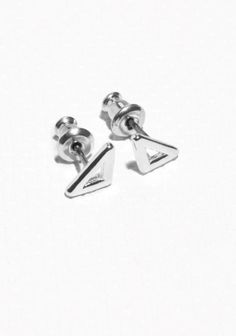 Delicate triangual frames shape these brass stud earrings with a shiny finish.
