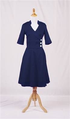 Crisp, clean lines of navy cotton combine with classic military detailing in the Carnival dress.  The double breasted bodice is finished with three contrasting buttons, while the wrap around skirt falls from the waist to create the perfect summer A-line.