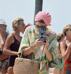 Princess of Monaco, Grace Kelly taking a photograph at a swimming competition at Palm Beach, Monte Carlo in 1972 (in Pucci).