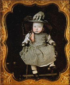 Mid 19th century photo of a child being steadied by a hand, most likely the mother....just a little creepy looking....