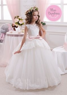 The Jasmine - a short sleeved princess dress with fitted lace bodice and a puffy floor-length skirt with a charming overskirt detail trimmed with delicate lace. The dress open back features a V-cut an