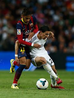 Angel Di Maria of Real Madrid is challenged by Neymar of Barcelona during the La Liga match between Real Madrid CF and FC Barcelona at the Bernabeu on March 23, 2014 in Madrid, Spain.