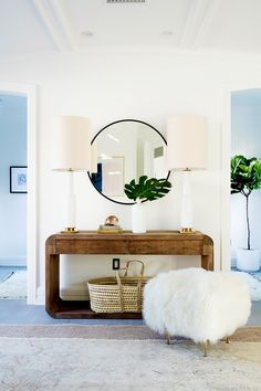 Entryway with round mirror and tall table lamps