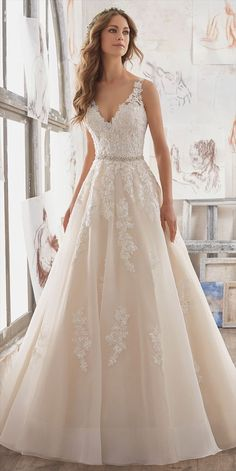 Breathtaking and Timeless, This A-Line Bridal Gown Features Crystal Beaded Alencon Lace Appliques on Organza. A Stunning Illusion Keyhole Back is Accented with Covered Button Detail.