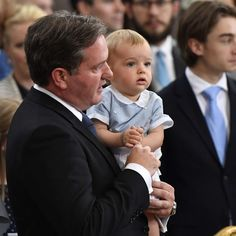 Chris O'Neill holds his son Prince Nicolas at Prince Oscar's christening