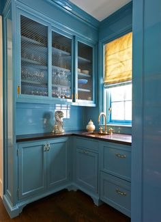 With an exuberant turquoise high gloss finish, the butler's pantry, adjacent to the dining room, family room and kitchen, stands on its own.