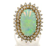 OPAL AND DIAMOND RING  Centring a cabochon white opal crystal claw set within a round brilliant cut diamond surround